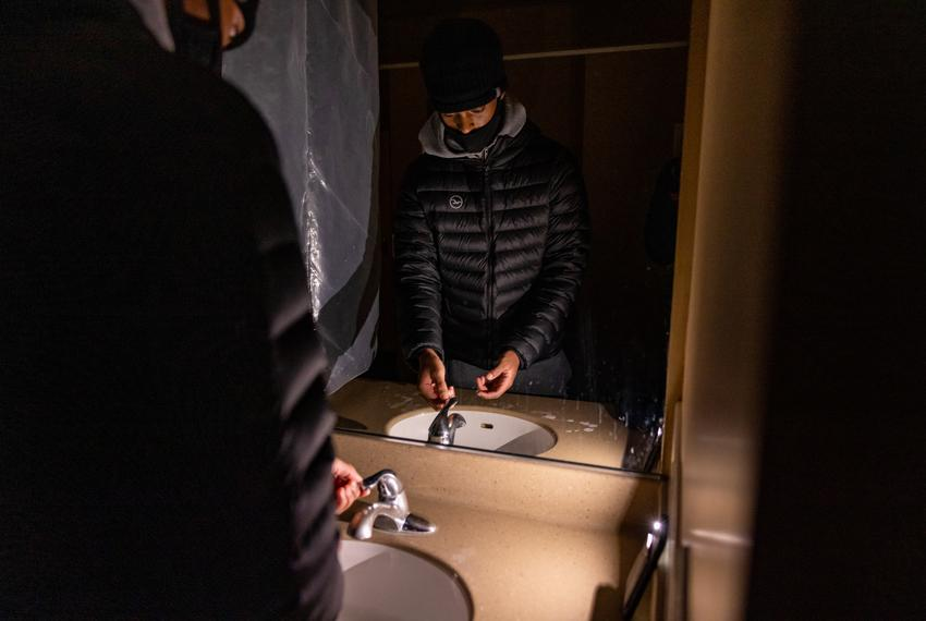 Nicholas Ware, a freshman computer science major at Texas State University, washes his hands in a dark bathroom using the fl…