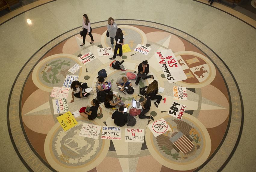 "A group of students against SB4, the ""sanctuary cities"" bill, sit in the rotunda of the Texas Capitol as the bill is being d…"