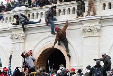 Pro-Trump rioters climb on walls at the U.S. Capitol during a protest against the certification of the 2020 U.S. presidential election results by Congress, in Washington, D.C., on Jan.6, 2021.