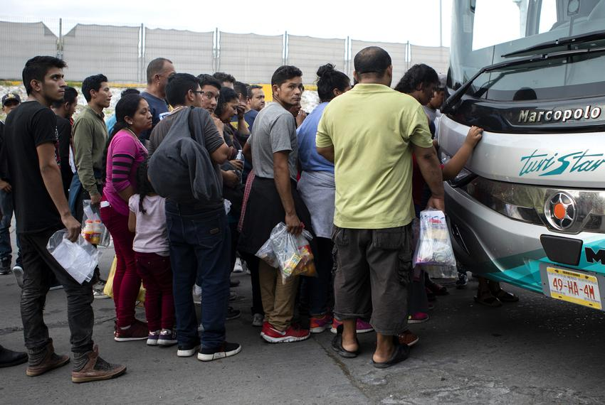 A group of migrants board a bus towards Monterrey at an immigration checkpoint in Nuevo Laredo. The group requested asylum i…