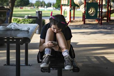 Halo Turner watches videos on her phone while with her family at Crescent Park in Frisco on June 23, 2021.