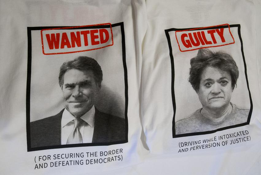 Front and back of T-shirts with Gov. Rick Perry and District Attorney Rosemary Lehmberg mugshots, provided by RickPAC at a M…