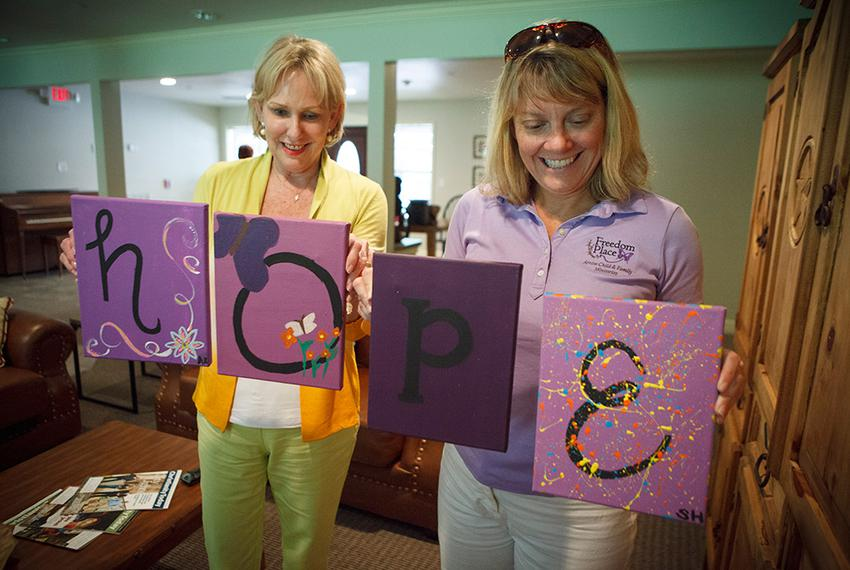 Executive Director Kellie Armstrong, right, and founder Nikki Richnow, left, showing some of paintings that the resident g...