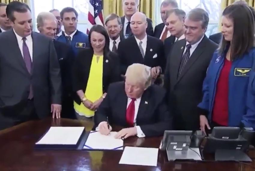U.S. Sen. Ted Cruz (far left) looks on as President Donald Trump signs the NASA authorization bill on March 21, 2017.