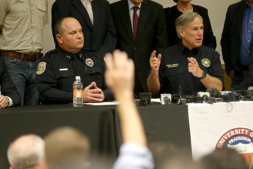 From left: Odessa Police Chief Michael Gerkeand Gov. Greg Abbot take questions from reporters at a press conference on the U…