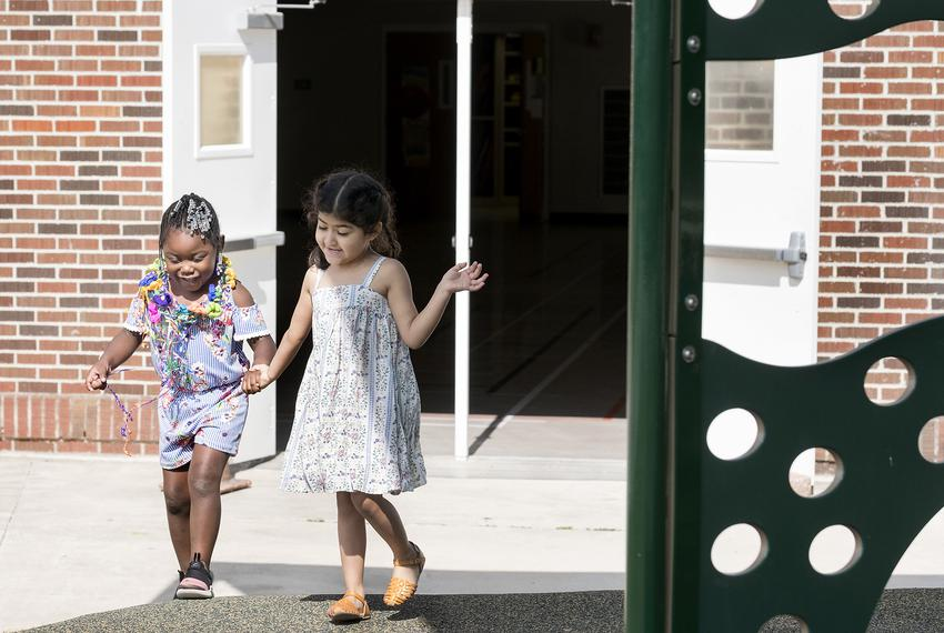 At Steele Montessori Academy, a formerly closed campus,  Azeri'aha and Penelope Acuña hold hands and play during recess on A…