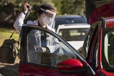Medical doctor Sandra Petersen wearing a face shield and mask grabs her work bag with her medical tools before seeing COVID-19 patients inside The Forum at Park Lane Assisted Living facility in Dallas, on Thursday, Dec. 10, 2020. Ben Torres for the Texas Tribune