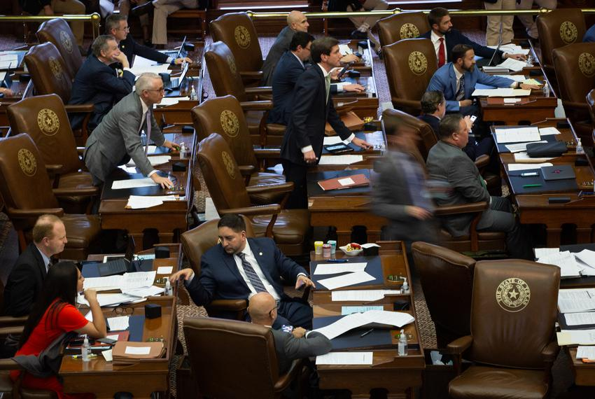 Members of the House move to vote at their desks on the House floor at the state Capitol on May 28, 2021.