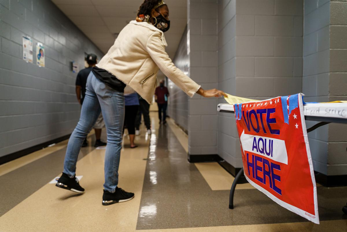 A voter picks up a copy of the ballot while they wait in line to vote at a polling location in Manor on Election Day. Nov. 3, 2020.