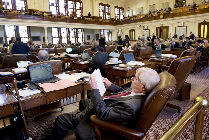 State Rep. Charlie Geren, R-Fort Worth, works from his desk on the House floor as the House debates the budget on April 6, 2…