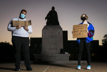 Shifa Rahman, left, and fellow protestor Blaise hold protest signs at the base of the William Marsh Rice statue on the campus of Rice University on Jan. 17, 2021. Rahman has spent an hour on campus every day calling for the removal of the statue since Aug. 31, 2020.