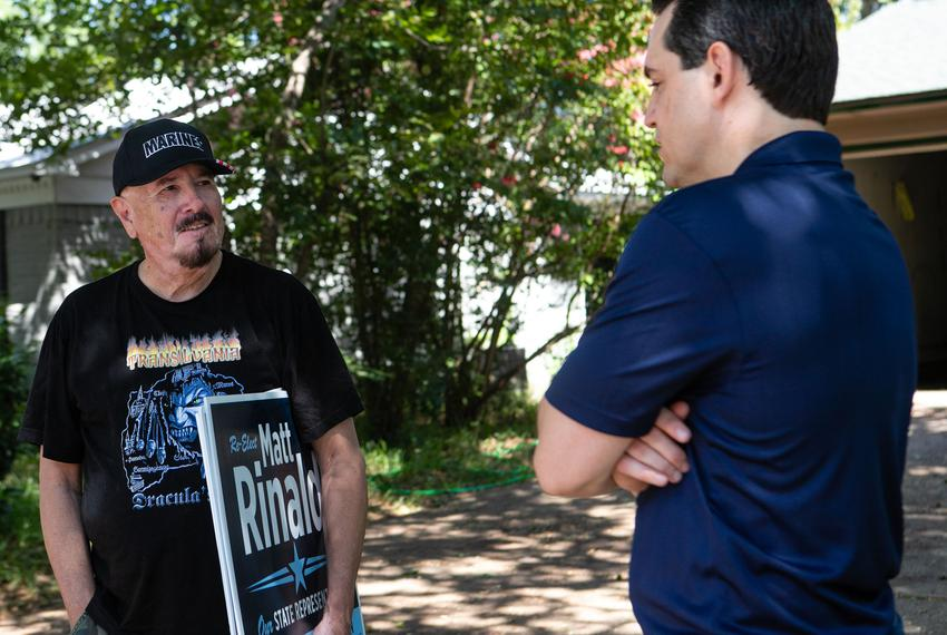 State Rep. Matt Rinaldi speaks with a Domingo, a supporter, while delivering yard signs in the Farmers Branch area of Texa...