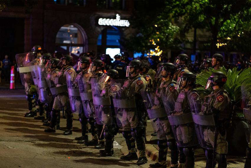 State Police in riot gear form a line along Congress Ave. and advance towards protesters to remove them from the street du...