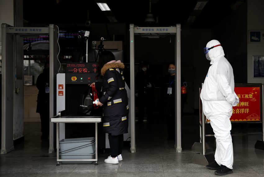 In the midst of an outbreak in China of the new coronavirus, a worker in a protective suit looks on as a woman enters a subway station in Beijing.