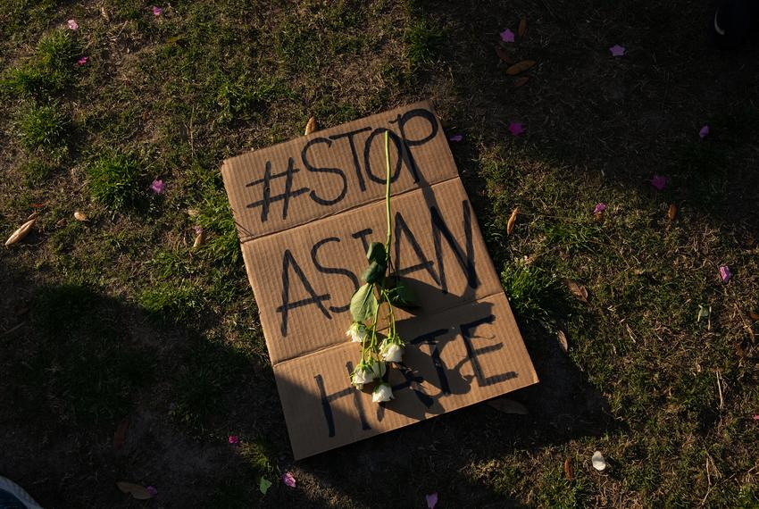 Flowers lay atop a sign at Discovery Green on March 20, 2021, in Houston. People gathered for the Stop Asian Hate Vigil and …