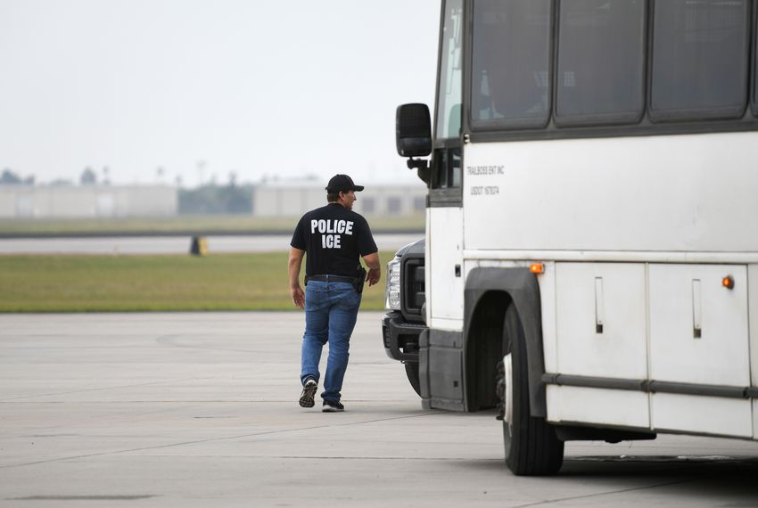 A law enforcement official walks past a transport bus used to carry migrants in U.S. Immigration and Customs Enforcement custody.