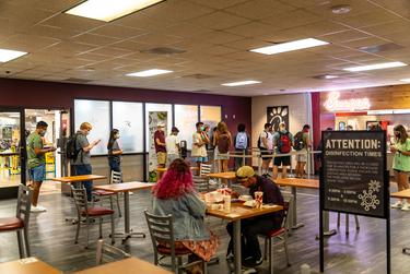 Students wait in line for food in the dining hall at the LBJ student center on the first day of classes at Texas State University in San Marcos on August 24, 2020.