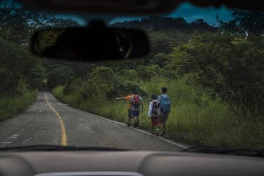 "Migrants walk through Highway México 307 on Oct. 21 near Palenque, Chiapas. The highway is also known by the locals as ""El Gran Corredor del Pacífico del Migrante,"" or ""The Great Pacific Corridor of the Migrant."" This is a common route for Honduran migrants due to the proximity to their country."