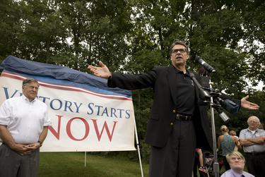 Former New Hampshire Gov. John Sununu looks on as Gov. Rick Perry speaks at a Stratham rally on Saturday.