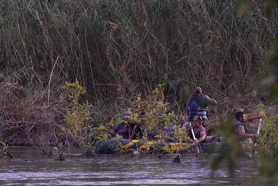 A raft loaded with undocumented immigrants navigates the Mexican side of the Rio Grande across from Ruperto Escobar's ranch in April 2016. The ranch sits along the Rio Grande, the international boundary between the U.S. and Mexico, in Starr County in South Texas. For generations smugglers have used the ranch to move people and product across the border, and Escobar doesn't see that changing anytime soon.