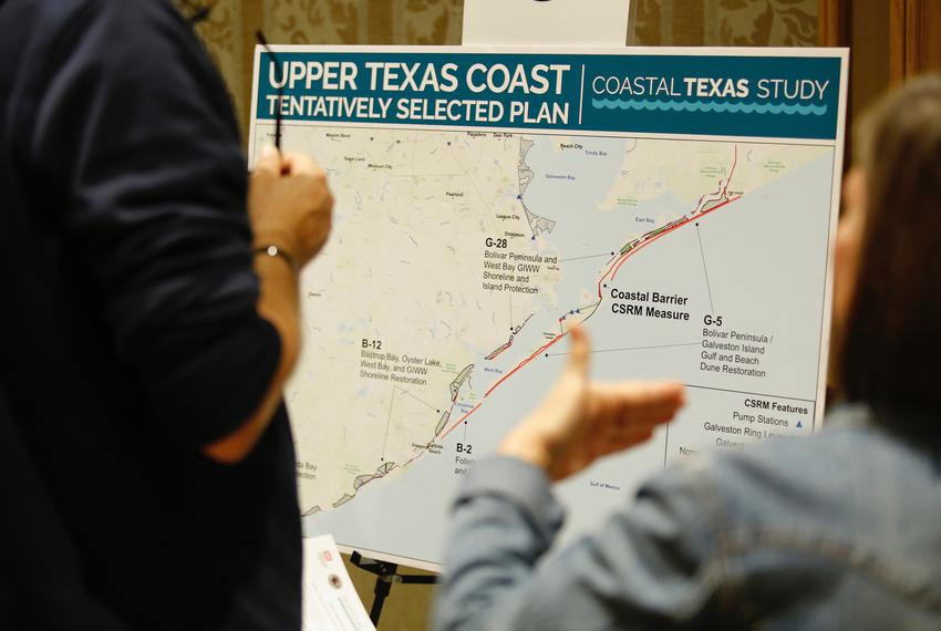 People discuss a map of the coastal spine at an Army Corp of Engineers meeting about the Texas Coastal Study, in Galveston o…