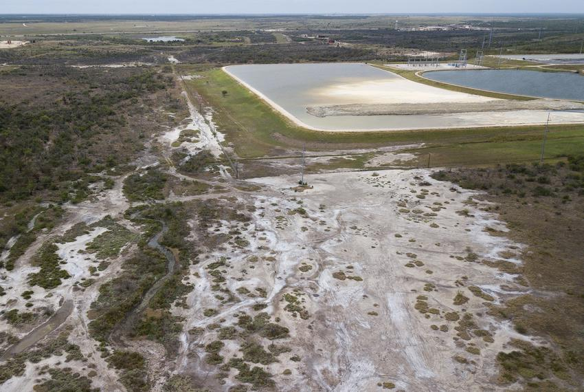 A fence separates the Peeler Ranch from property owned by the San Miguel Electric Cooperative. A coal ash pond operated by t…