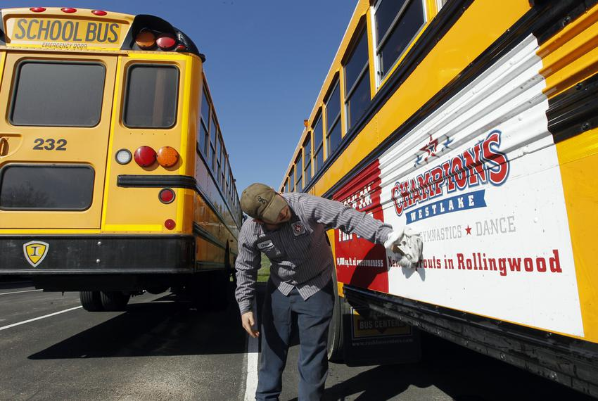 Eanes ISD school bus mechanic Chase Roberts washes the dirt off the advertising on buses in West Lake Hills, Texas, on Feb. …