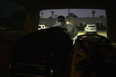 Juan Lopez wheels a stretcher with a body on it into his Cadillac Escalade. Lopez picks up dead bodies from homes and hospitals and delivers them to local funeral homes. July 17, 2020.
