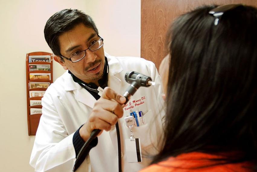 Dr. Xavier Muñoz treats a patient in El Paso. Muñoz agreed to treat low-income, underinsured patients in return for having h…