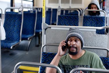 Dallas resident Hiireen Jones talks on the phone on a DART bus on its way to Irving.