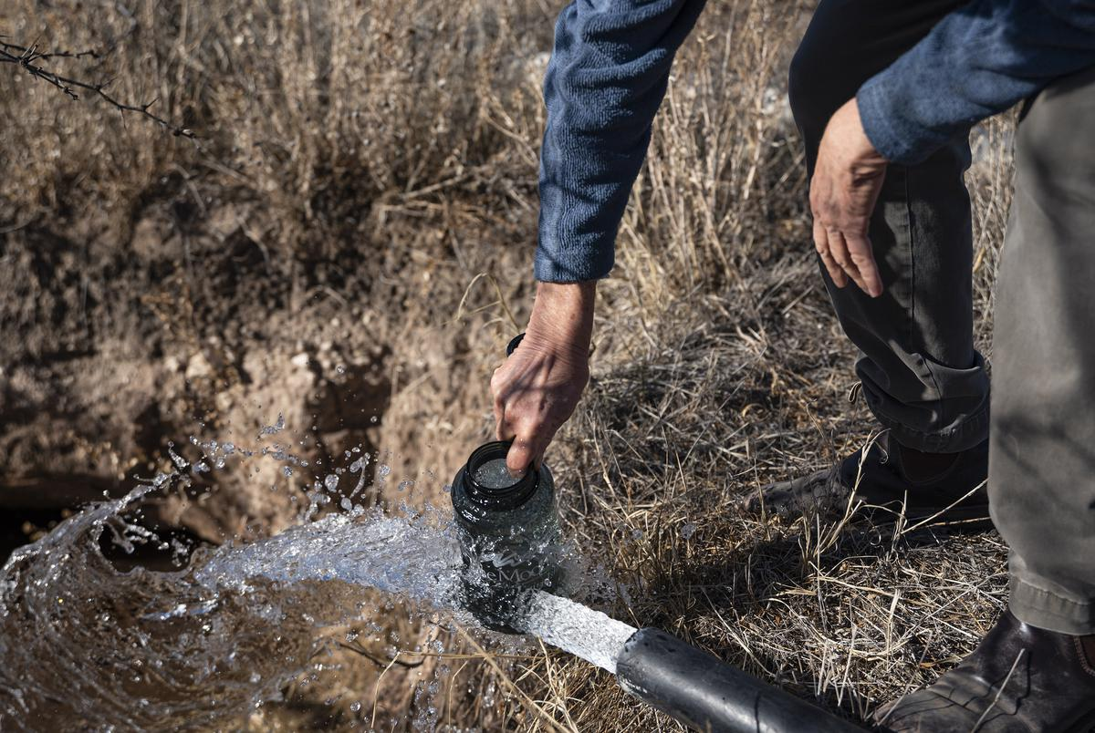 Elaine Magruder fills a water bottle from a well on her ranch Sunday, Jan. 17, 2021 near Andrews, Texas.