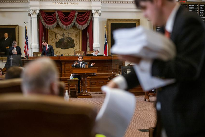 A staffer passes out papers while state Rep. Diego Bernal, D-San Antonio, speaks during session on the House floor at the st…