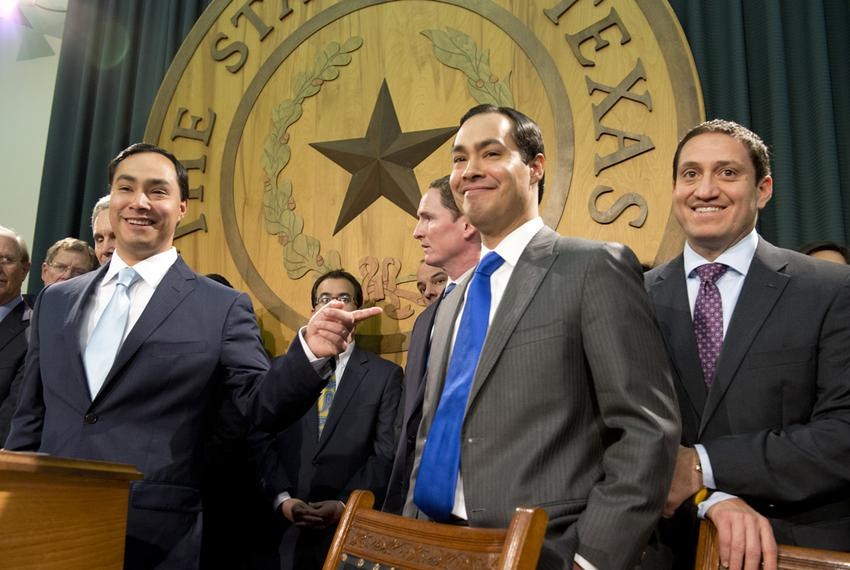 U.S. Congressman Joaquin Castro (l) points at his brother Julián Castro at a 2013 press conference.