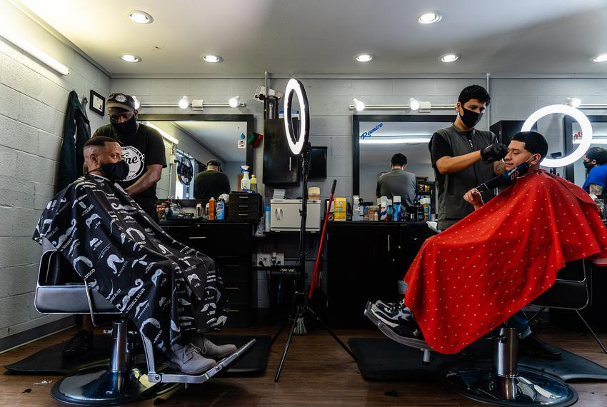 Stevin Kane and Ramiro Cruz give haircuts to customers, after Kane's Barbershop reopened from being closed due to the coro...