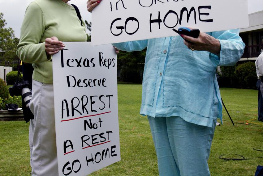 From left, Carolyn Wallace and Marjorie Brown of Ardmore, Oklahoma hold signs outside the motel where Texas Democratic state…