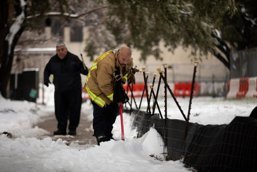 Firefighters clear snow and ice from a side walk outside of the Rebekah Baines Johnson Center in East Austin on Feb. 17, 202…