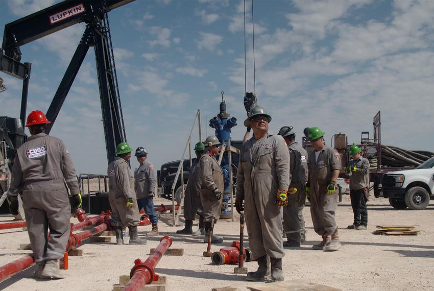 "Workers prepare to hydraulically fracture — or ""frack"" — an oil well northwest of Midland. 