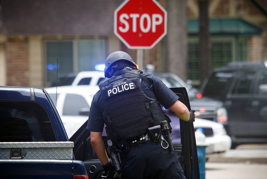 A Houston police officer on the scene in a west Houston neighborhood where a gunman with an assault rifle shot one man and injured six before being killed by a SWAT officer on May 29, 2016.