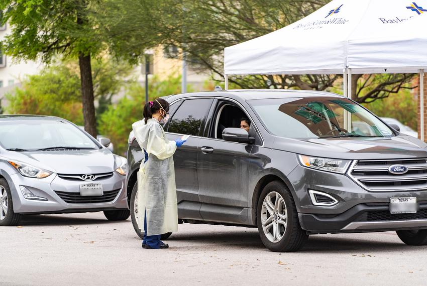 A medical professional wearing protective clothing administers a test to a patient at a drive-through COVID-19 testing facil…