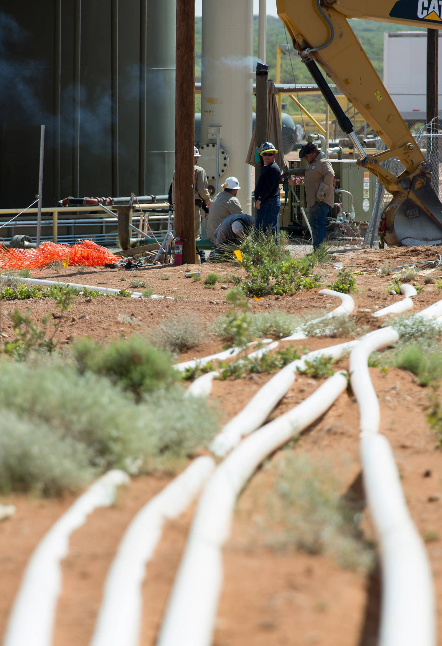 Workers repair oil and gas equipment on public land near Carlsbad, N.M., on May 24, 2018.