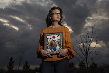 Tina Jones poses with a portrait of her husband Brian Jones in the pecan orchard he planted when they first moved onto their new land in Ennis. They watched the saplings grow into trees over 18 years, and during the fall of 2020 they for the first time grew enough pecans for Brian to make a pecan pie. Brian passed at the age of 52 on January 12 from COVID-19.    Tina Jones identifies as female, Caucasian, non-latino.