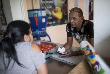 Reinaldo Ramirez Pacheco of Cuba talks to his wife in the rectory at El Buen Pastor migrant shelter in Ciudad Juárez on May 13, 2019. They have been at the shelter for two months.
