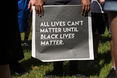 """A demonstrator holds his sign at a rally for George Floyd in Vidor on June 06, 2020. Organizers of the rally in Vidor, historically known as a """"sundown town,"""" said they wanted to change the reputation and move on from the past."""
