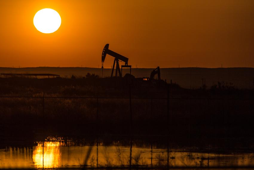 A pump jack operates at sunrise just off Pecos Highway in Carlsbad, N.M., on May 24, 2018.