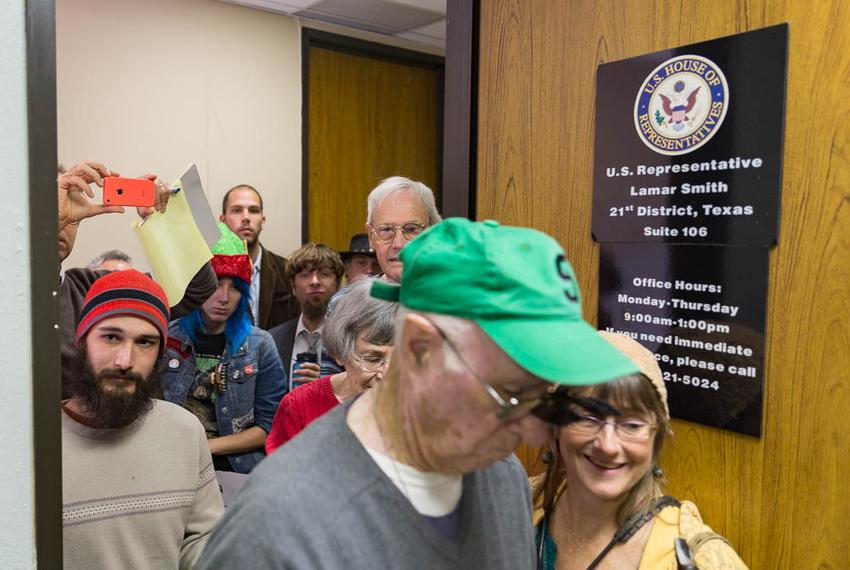 "Climate change activists crowd Representative Lamar Smith's office to present him with the ""Flat Earth Foundation of Texas..."