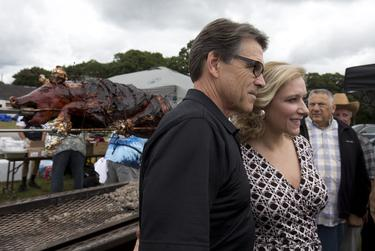 Gov. Perry poses with retired United States Marine Corps Sgt. Jessie Jane Duff at the Defend Freedom Pork Roast in Rochester, N.H. Aug. 23, 2014