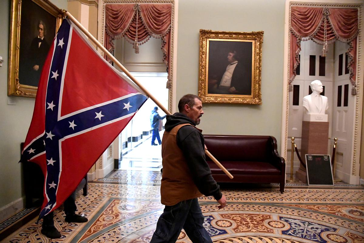 A supporter of President Donald Trump carries a Confederate battle flag on the second floor of the U.S. Capitol near the entrance to the Senate after breaching security defenses, in Washington, U.S., on Jan. 6, 2021.