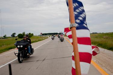 A group of veterans and supporters ride with Governor Rick Perry from Perry to Boone, Iowa, on June 6, 2015, as part of the Ride with Rick event. The fundraiser benefited the Puppy Jake Foundation, an organization that trains service dogs for wounded veterans.