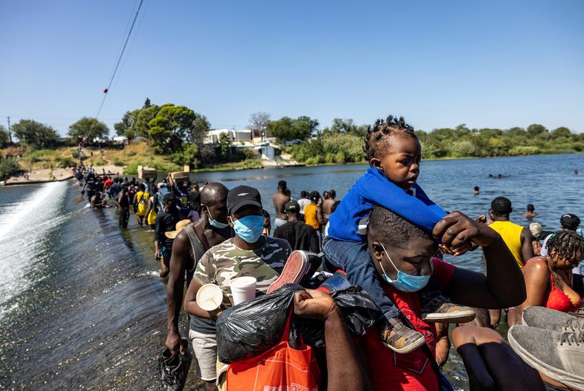 Migrants cross the Rio Grande between Del Rio and Ciudad Acuña to bring supplies back to a temporary migrant camp under the …