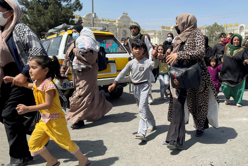 Women with their children try to get inside Hamid Karzai International Airport in Kabul, Afghanistan, on Aug. 16, 2021.